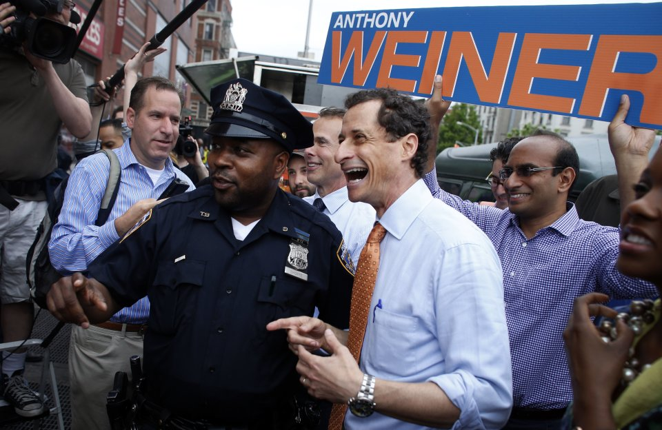 New York City mayoral hopeful Anthony Weiner laughs with a police officer while greeting commuters during a campaign event outside a Harlem subway station, Thursday, May 23, 2013 in New York. Weiner, who ran for mayor in 2005 and nearly did in 2009, is getting into the race to succeed three-term Mayor Michael Bloomberg about two years after a series of tawdry tweets, and obfuscating explanations that capsized his promising congressional career. (AP Photo/Jason DeCrow)