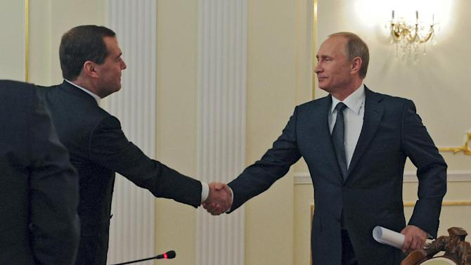 Russian President Vladimir Putin, right, and Russian Prime Minister Dmitry Medvedev shake hands at a Cabinet meeting in the Novo-Ogaryovo residence outside Moscow, Wednesday, Oct. 29, 2014. (AP Photo/RIA-Novosti, Mikhail Klimentyev, Presidential Press Service)
