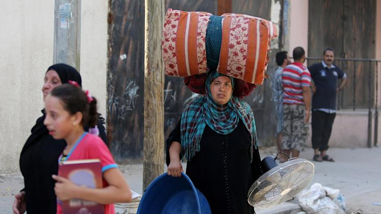 A Palestinian woman carries her belongings she salvaged from her house during a 12-hour cease-fire in Gaza City's Shijaiyah neighborhood, Saturday, July 26, 2014. Thousands of Gaza residents who had fled Israel-Hamas fighting streamed back to devastated border areas during a lull Saturday to find large-scale destruction: scores of homes were pulverized, wreckage blocked roads and power cables dangled in the streets. (AP Photo/Hatem Moussa)