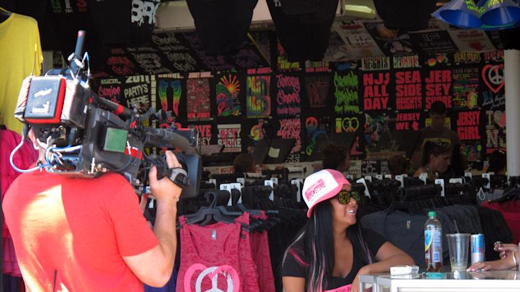 "In this July 15, 2011 photo, MTV cameras film Nicole ""Snooki"" Polizzi during the taping of a ""Jersey Shore"" episode on the Seaside Heights, N.J., boardwalk. A New Jersey assemblyman introduced a law on Monday, Sept. 24, 2012, that would let towns regulate the filming of reality TV shows within their borders, including charging for the cost of extra police protection. (AP Photo/Wayne Parry)"