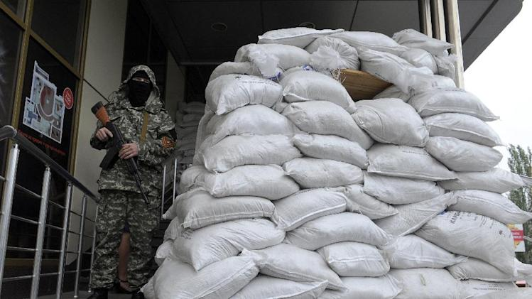 An armed pro-Russian militant guards a building where members of Ukraine's National Guard were being held and freed by pro-Russian rebels, on June 27, 2014 in Donetsk