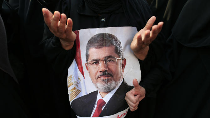 "Supporters of ousted President Mohammed Morsi pray in Nasr City, Cairo, Egypt, Tuesday, July 9, 2013. Arabic reads, ""No substitute for the legitimacy."" After days of deadlock, Egypt's military-backed interim president named a veteran economist as prime minister on Tuesday and appointed pro-democracy leader Mohamed ElBaradei as a vice president, while the army showed its strong hand in shepherding the process, warning political factions against ""maneuvering"" that impedes the transition. (AP Photo/Hassan Ammar)"