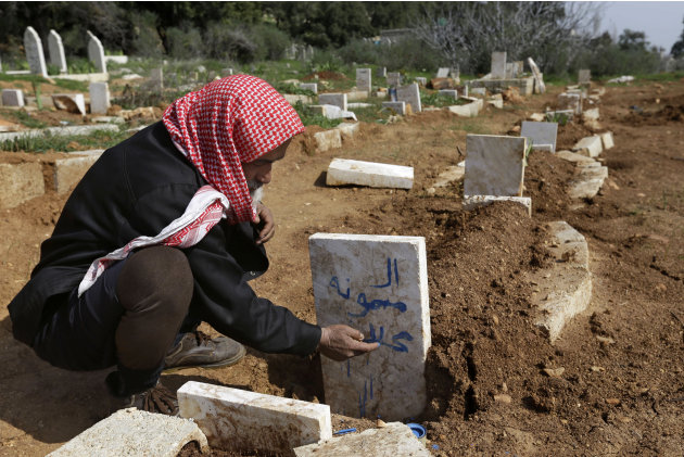 A Syrian villager, Abu Ibrahim, 73, writes the name of his granddaughter on her grave who was killed from an airstrike by Syrian government forces, at Jabal al-Zaweya village of Sarja, in Idlib, Syria