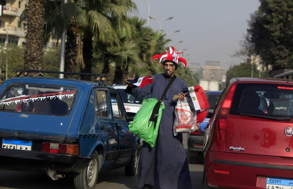 An Egyptian flags vender walks down a traffic line, in Cairo, Egypt, Monday, Feb. 14, 2011. Egypt's ruling military council has issued a new communique calling on labor leaders to stop strikes and protests to allow a sense of normalcy to return to the country. (AP Photo/Amr Nabil)