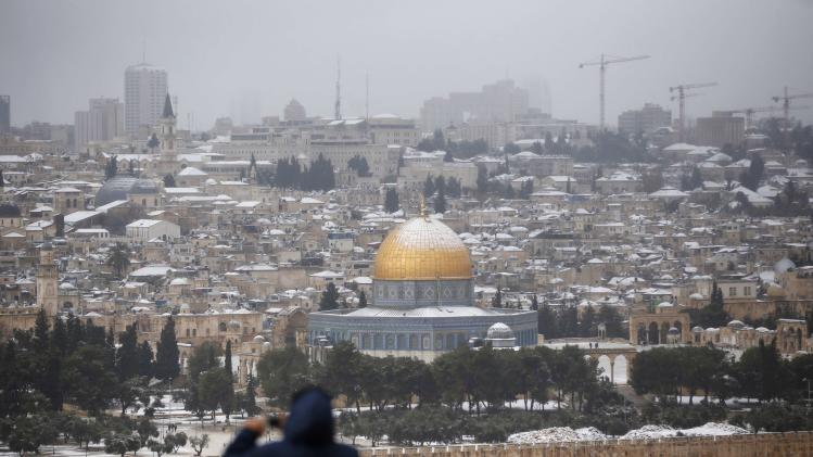 The snow capped Dome of the Rock in Jerusalem's Old City is seen from the Mount of Olives