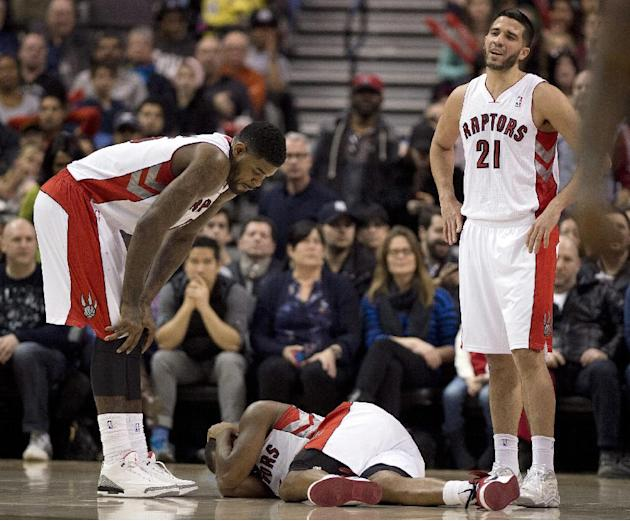 Toronto Raptors forward Amir Johnson, left, and guard Greivis Vasquez (21) stand near as guard Kyle Lowry lies on the floor injured during the second half of an NBA basketball game against the Phoenix