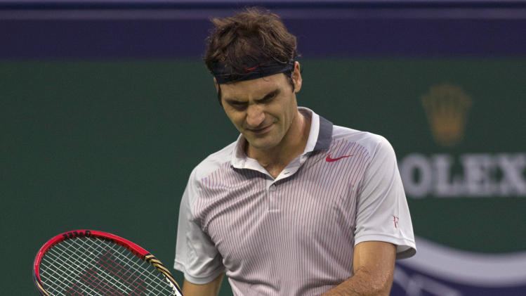 Switzerland's Roger Federer reacts to losing a point during a match against France's Gael Monfils at the Shanghai Masters tennis tournament at the Qizhong Forest Sports City Tennis Center in Shanghai, China, Thursday, Oct. 10, 2013. Monfils won 6-4, 6-7, 6-3. (AP Photo/Ng Han Guan)