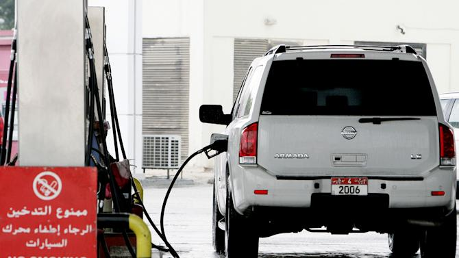 In this Saturday, Dec. 1, 2012 photo, a man, unseen, fills his car with gasoline at a gas station in Doha, Qatar. The host of the current U.N. climate talks, Qatar, is among dozens of nations that keep gas prices low through subsidies that exceeded $500 billion globally last year. (AP Photo/Osama Faisal)
