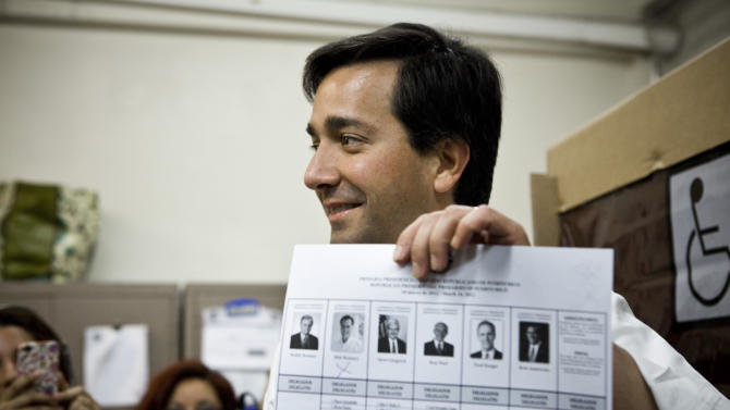 """Puerto Rico's Governor Luis Fortuno shows his ballot to the press after marking it with an """"x"""" under the photo of candidate Mitt Romney during the Republican presidential primary election at San Jose Academy in Guaynabo, Puerto Rico, Sunday March 18, 2012. Puerto Rico's residents cannot vote in general elections, but are set to award 20 delegates in their Sunday Republican primary.  (AP Photo/Christopher Gregory)"""