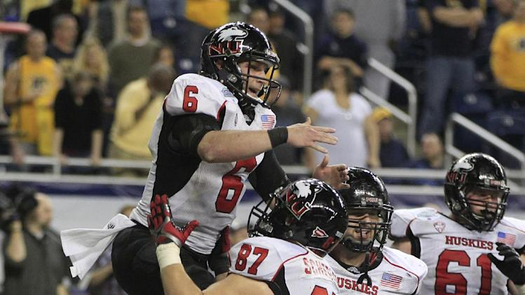Northern Illinois quarterback Jordan Lynch (6) jumps onto teammate Jason Schepler after scoring a touchdown during the overtime period of the Mid-American Conference championship NCAA college football game against Kent State, Friday, Nov. 30, 2012. Northern Illinois defeated Kent State 44-37 in two overtimes. (AP Photo/Carlos Osorio)