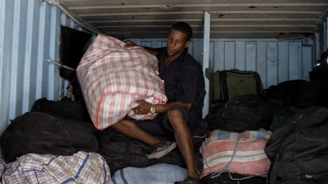 In this Aug 29, 2012 photo, Luis Manuel Dlas works to unload bags of imported clothing and accessories from a storage container, where self-employed vendors store their merchandise within an open market where the government allows licensed vendors to sell their goods in downtown Havana, Cuba. A jump in import taxes on Monday, Sept. 3 threatens to make life tougher for some of Cuba's new entrepreneurs who the government has been trying to encourage as it cuts a bloated workforce in the socialist economy.  In Cuba, the average monthly wage is about $20. (AP Photo/Franklin Reyes)
