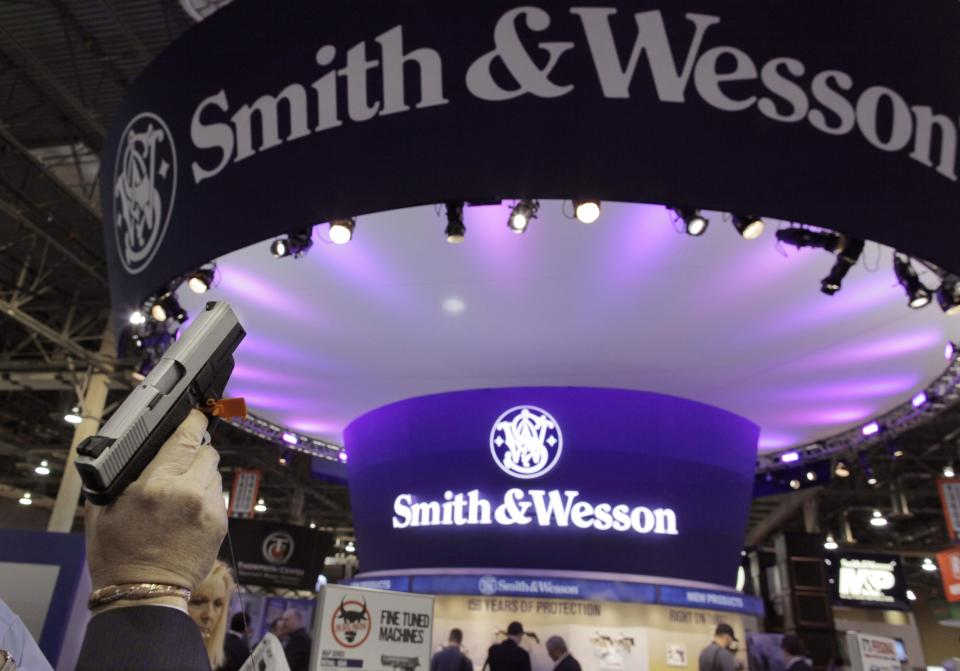 A firearms retailer examins a Smith & Wesson hand gun at the Shooting, Hunting and Outdoor Trade show, Tuesday, Jan. 18, 2011 in Las Vegas. (AP Photo/Julie Jacobson)