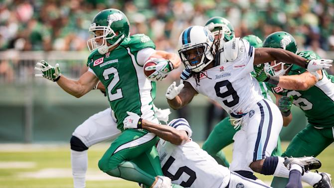 Saskatchewan Roughriders wide receiver Ryan Smith (2) tries to escape Toronto Argonauts safety Jermaine Gabriel (5) and Toronto Argonauts defensive back Akwasi Owusu-Ansah (9) during the first half of their CFL football game in Regina
