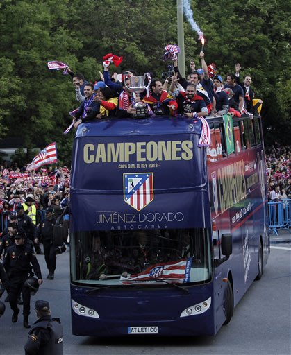 Atletico de Madrid's players celebrate on top of an open top bus in Madrid, Spain, Saturday, May 18, 2013. Atletico de Madrid defeated Real Madrid in the Copa del Rey final soccer match on Friday
