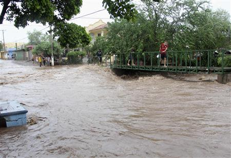 People cross a bridge as a river overflows its banks and floods a neighbourhood in Culiacan