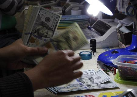 money changer counts U.S. dollar bills at a currency exchange in