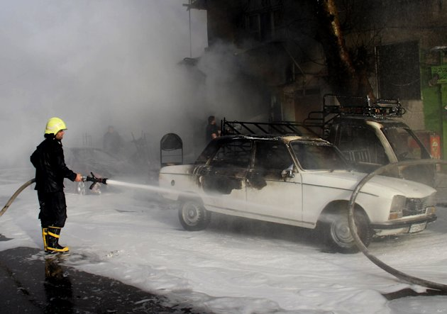 In this photo released by the Syrian official news agency SANA, a Syrian firefighter extinguishes a burned car at the scene where two mortar rounds exploded near an orphanage, at al-Boukhtyar area, in