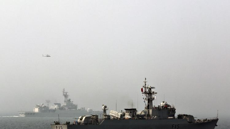 A helicopter flies past as Bangladesh's naval frigate BNS Abu Bakar participates in multi-country maritime joint exercises off the coast in Qingdao