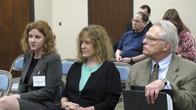 In this April 13, 2012 photo, Dr. Ann Kristin Neuhaus, center, of Nortonville, Kan., accused of performing inadequate mental health exams on young patients she referred to the late Dr. George Tiller for late-term abortions, sits between her attorneys, Kelly Kauffman, left, and Bob Eye, at a State Board of Healing Arts meeting in Topeka, Kan. The board regulates Kansas doctors. Kansas regulators are expected to decide Friday, June 21, 2012 whether to revoke the Nuehaus' medical license. (AP Photo/John Hanna)