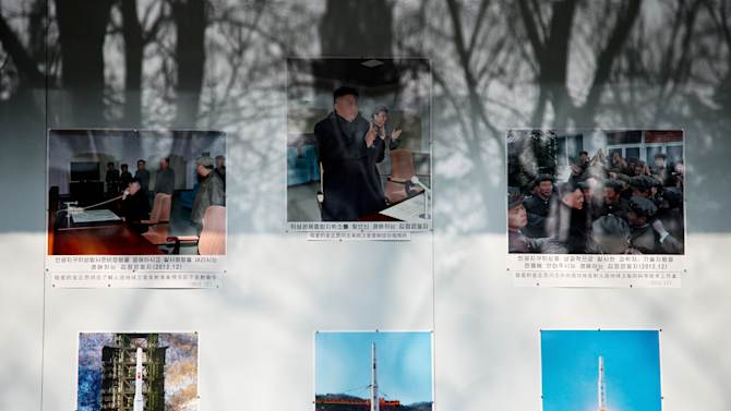 """Trees are reflected on a board displaying photos of North Korean leader Kim Jong Un and the country's successful long range rocket launch outside North Korean embassy in Beijing Tuesday, Feb. 12, 2013. North Korea apparently conducted a widely anticipated nuclear test Tuesday, strongly indicated by an """"explosion-like"""" earthquake that monitoring agencies around the globe said appeared to be unnatural. There was no confirmation from Pyongyang that it had conducted a test, which it has been threatening for weeks. (AP Photo/Andy Wong)"""