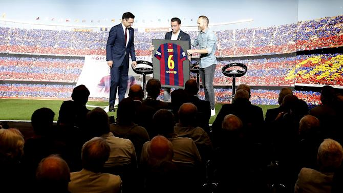 Barcelona's Xavi Hernandez shows Barcelona jersey signed by the whole team between President Josep Maria Bartomeu and his teammate Andres Iniesta during Xavi's farewell event at Auditori 1899 in Nou Camp stadium in Barcelona