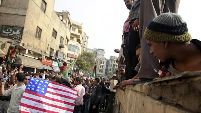 """Protesters chant slogans and carry a desecrated representation of an American flag during demonstrations against the Israeli invasion of Gaza, while marching through the streets towards Tahrir square after Friday prayers in Cairo, Egypt, Friday, Nov.16, 2012. In his Friday sermon at Al-Azhar mosque, influential cleric Sheikh Yusuf al-Qaradawi, not shown, said the Islamic world would not be silent in the face of Israel's military operation in Gaza. Arabic writing reads, """"death to Israel and death to America."""" (AP Photo/Thomas Hartwell)"""