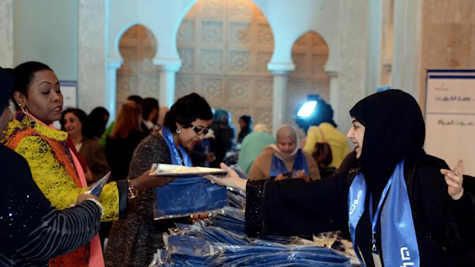 In this Tuesday, Nov. 27, 2012 photo, A Kuwait election campaign volunteer, right, gives away candidate's shirts during an election seminar in Al Bidaa, Kuwait City. The drama of Kuwait's parliamentary elections has nothing to do with the ballot count. It's what may come after that has the country on edge as a broad coalition of conservative Islamists, liberal reformers and others vow to boycott Saturday's voting. (AP Photo/Gustavo Ferrari)