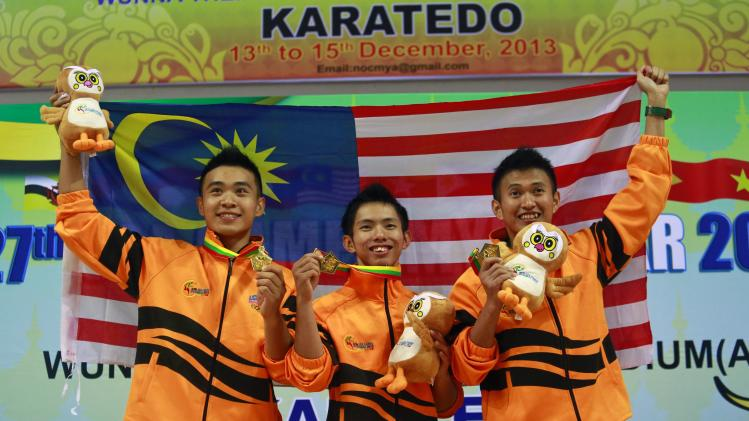 Gold medallists from Malaysia pose with their medals after winning the male team Kata at Karatedo event during the 27th SEA Games in Naypyitaw