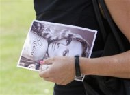 A mourner leaves, holding a picture of model Reeva Steenkamp, after her memorial service at the Victoria Park Crematorium in Port Elizabeth February 19, 2013. Steenkamp&#39;s boyfriend Olympic and Paralympic athlete Oscar Pistorius has been charged with her murder. REUTERS/Rogan Ward