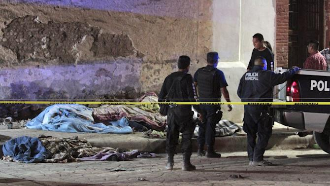 Policemen stand next to bodies of pilgrims covered with blankets, at the site of an accident in the town of Mazapil