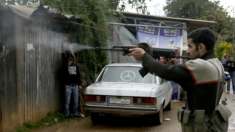 A Sunni gunman fires his weapon during clashes that erupted between pro and anti-Syrian regime gunmen in the northern port city of Tripoli, Lebanon, Wednesday, Dec. 5, 2012. Gunmen loyal to opposite sides in neighboring Syria's civil war battled in the streets of northern Lebanon and the death toll from two days of fighting was at least five killed and 45 wounded, officials said. The fighting comes at a time of deep uncertainty in Syria, with rebels closing in on President Bashar Assad's seat of power in Damascus. (AP Photo/Hussein Malla)