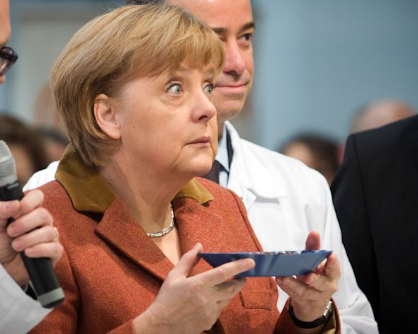 German Chancellor Angela Merkel looks up after smelling at coffee beans during the opening tour of the &#39;International Green Week&#39; inBerlin, Germany, Friday, Jan. 18, 2013. International Green Week opens to the public from Jan. 18 until Jan. 27, 2013. (AP Photo/dpa, Michael Kappeler)