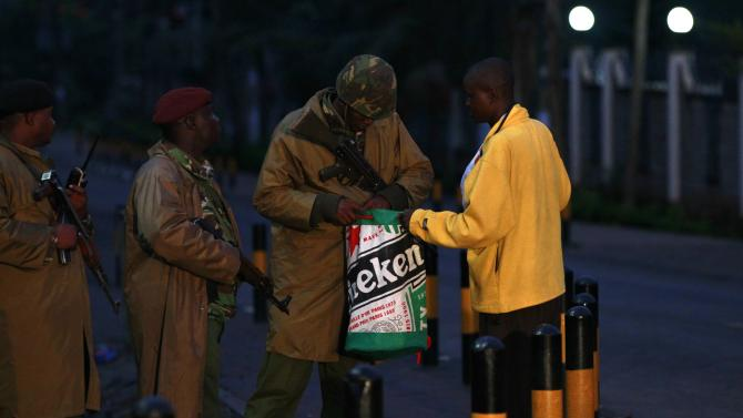 Kenyan policemen search a man as he walks past the Westgate Shopping Centre in the capital Nairobi