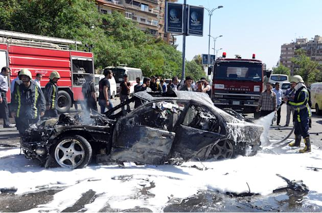 This photo released by the Syrian official news agency SANA, shows Syrian fire fighters extinguishing burning cars after a car bomb exploded in the capital's western neighborhood of Mazzeh, in Damascu