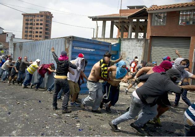 Demonstrators pull a container to use it as a roadblock during a protest against the government of Venezuelan President Nicolas Maduro in San Cristobal, on February 24, 2014