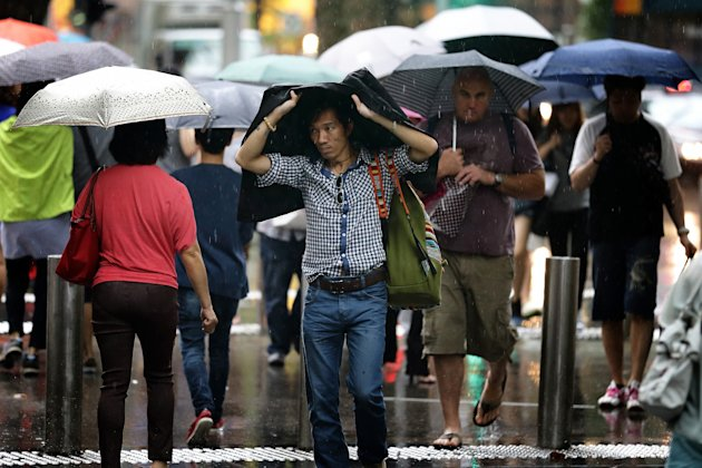 SINGAPORE - FEBRUARY 14:  Shoppers brave the rain along Orchard Road on February 14, 2013 in Singapore. The government white paper revealed Singapore&#39;s population may increase 30% to over 6.9 million by 2030, with nearly half the population expected to be foreign-born. Many local residents are critising the plan, concerned about the added strain on housing, transportation and healthcare and the diminishing identity of the Singaporean community.  (Photo by Suhaimi Abdullah/Getty Images)