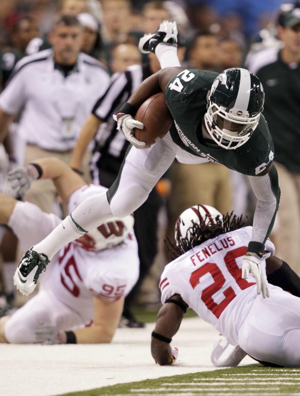 Michigan State's Le'Veon Bell is tackled by Wisconsin's Antonio Fenelus during the first half of the Big Ten conference championship NCAA college football game, Saturday, Dec. 3, 2011, in Indianapolis. (AP Photo/AJ Mast)