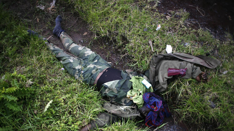 The body of a Congolese army soldier is seen in a ditch on the road to Rushuru in Buhumba some 25 kilometers (16 miles) north of Goma, Thursday, Nov. 22, 2012. M23 Rebel spokesman Lt. Col. Vianney Kazarama vowed Thursday that the fighters would press forward toward seizing the strategic eastern town of Bukavu, which would mark the biggest gain in rebel territory in nearly a decade if it were to fall. (AP Photo/Jerome Delay)