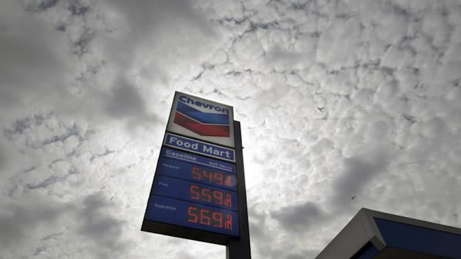 "FILE - In this Tuesday, Oct.  9, 2012, file photo, a Chevron station posts gasoline prices starting at $5.50 per gallon in downtown Los Angeles. Shares of Chevron Corp. plunged Wednesday after the oil giant said its third-quarter earnings are expected to be ""substantially lower"" than in the second quarter. (AP Photo/Reed Saxon, File)"