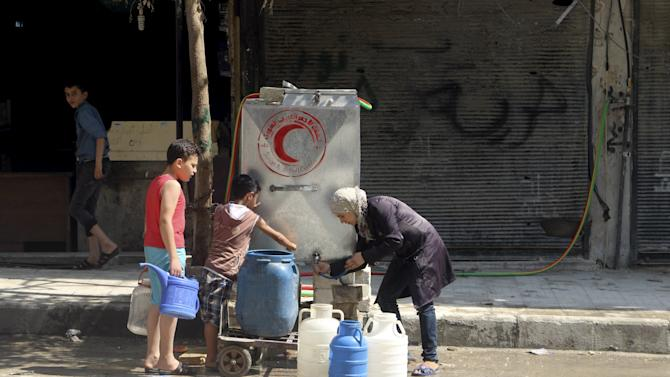 Residents fill containers with water in Aleppo's eastern district of Tariq al-Bab, Syria