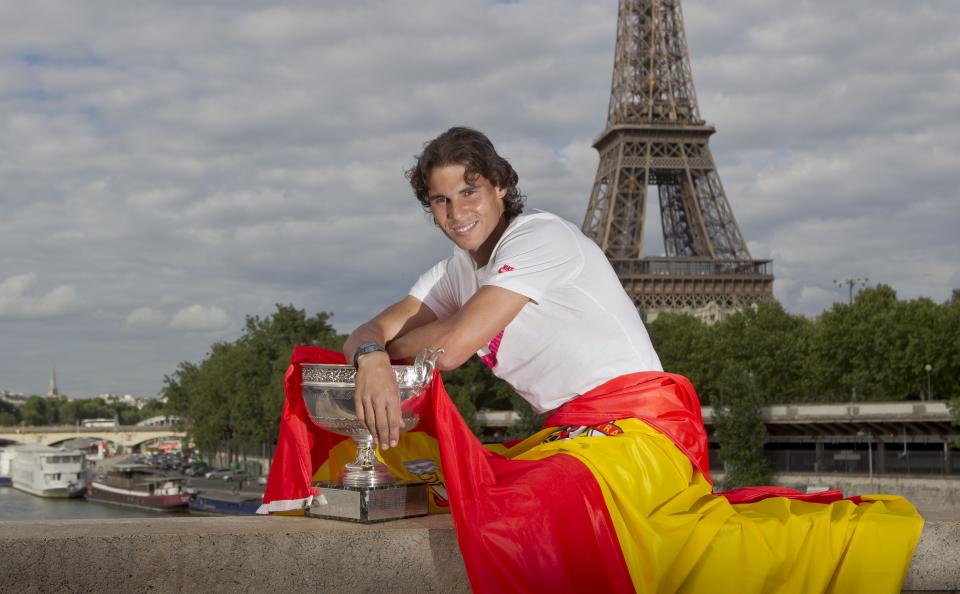 Rafael Nadal of Spain poses with the trophy and the Spanish flag after winning the mens final match against Novak Djokovic of Serbia at the  French Open tennis tournament in Paris, Monday June 11, 2012. Eiffel Tower and Seine river in the background. (AP Photo/Michel Euler)