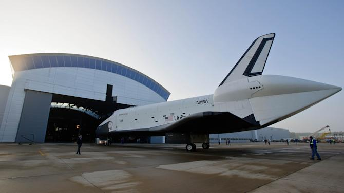 In this photo provided by NASA, space shuttle Enterprise rolls from the space hangar at the Steven F. Udvar-Hazy Center prior to a transfer ceremony, Thursday, April 19, 2012, in Chantilly, Va. Space shuttle Discovery on Thursday will take Enterprise's place representing the nation's shuttle program at the National Air and Space Museum's Udvar-Hazy Center, becoming the first orbiter flown in space to go on public display. (AP Photo/NASA, Paul E. Alers)
