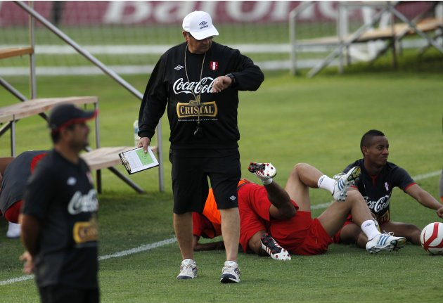 Peru's national soccer team coach Sarkarian checks his watch after a training session in Lima