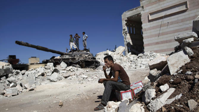 A Syrian man smokes a cigarette sitting next to the rubble of a damaged mosque in the city of Azaz, on the outskirts of Aleppo, Syria, Wednesday, Aug. 22, 2012. (AP Photo/Muhammed Muheisen)