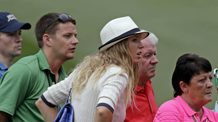 Tennis player Caroline Wozniacki watches Rory McIlroy, of Northern Ireland, with his father Gerry, right, during the first round of the Masters golf tournament Thursday, April 11, 2013, in Augusta, Ga. (AP Photo/David Goldman)