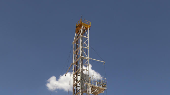 FILE - In this Friday, July 20, 2012 file photo, a drilling rig is pictured near Calumet, Okla. America's decision to re-elect President Barack Obama over Republican presidential candidate, former Massachusetts Gov. Mitt Romney will impact key sectors of the American economy. The boom in U.S. oil and gas production during the president's first term will likely continue, thanks largely to new drilling techniques. But drilling could slow if the Environmental Protection Agency toughens rules governing a controversial technique called hydraulic fracturing. (AP Photo/Sue Ogrocki)