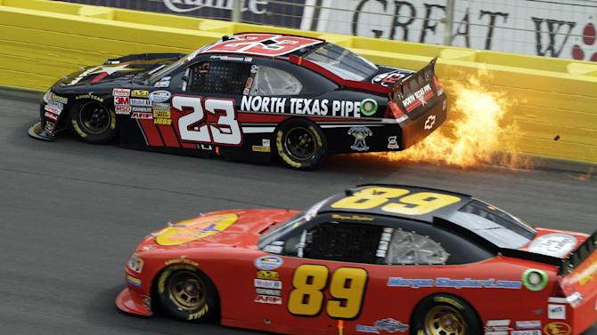 Flames stream from the car of Robert Richardson Jr. (23) as Morgan Shepherd (89) drives past during the NASCAR History 300 Nationwide series auto race in Concord, N.C., Saturday, May 26, 2012. (AP Photo/Bob Jordan)