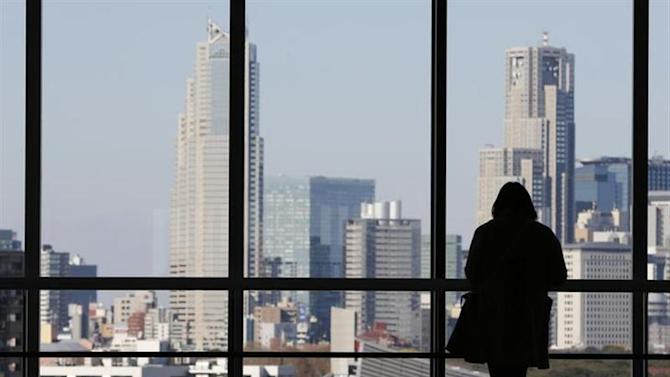 A woman looks at highrise buildings in Tokyo December 13, 2012. REUTERS/Yuriko Nakao/Files