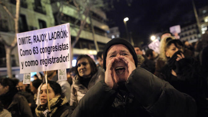 FILE - In this Jan. 18, 2013 file photo, people shout slogans as they protest against corruption outside the Popular Party's headquarters in central Madrid. In an announcement Monday Jan. 21, 2013, Spain's governing Popular Party says it will commission an external audit of its finances to clear its name several days after Spain's National Court said that an investigation it began in 2009 about allegations of irregular party financing found that former party Treasurer Luis Barcenas had amassed an unexplained euro 22 million ($29 million) in a Swiss bank account. Spanish newspapers have alleged that he regularly distributed under-the-table bonuses to party leaders. Banner reads 'Resign Rajoy thief'. (AP Photo/Andres Kudacki File)