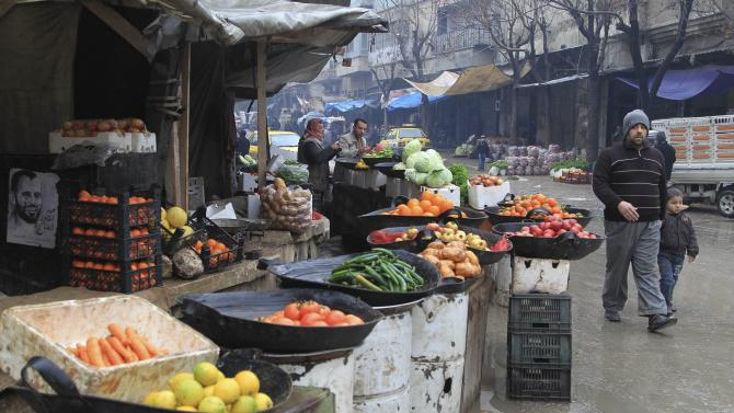 A man and a boy walk past fruits and vegetables displayed for sale in the old city of Aleppo